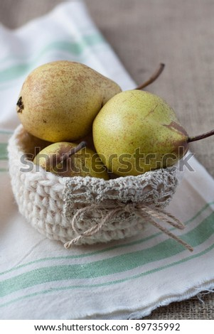 Closeup of pears in a crochet basket on hessian - stock photo