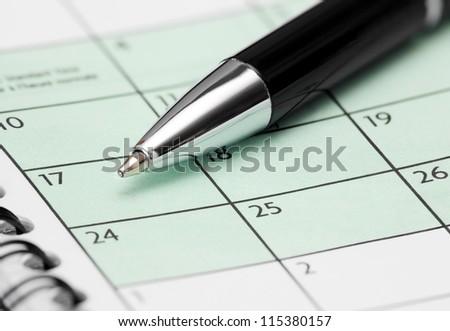 Closeup of Pen on Calendar Page - stock photo