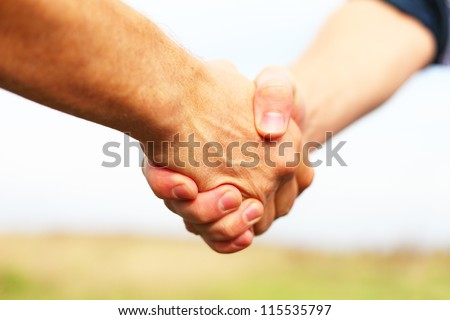 Closeup of people shaking hands - stock photo