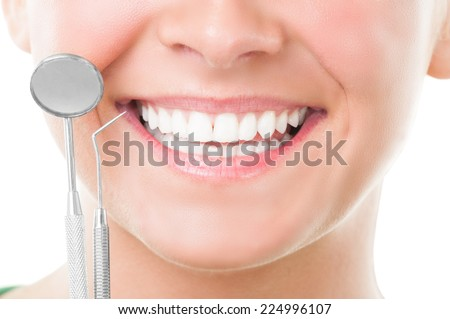 Closeup of perfect smile and dentist tools on white background - stock photo
