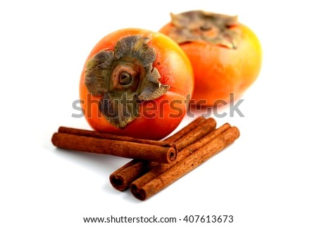 Closeup of persimmons and cinnamon on white background. - stock photo