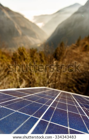 Closeup of photovoltaic solar panels in mountainous area, gathering sunlight. Sustainable resources, environmental conservation, alternative power source and generation, green energy concept.   - stock photo