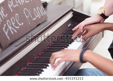 Closeup of piano keyboard . Man playing piano while lady explaining him something. Professional musician playing outdoors. - stock photo