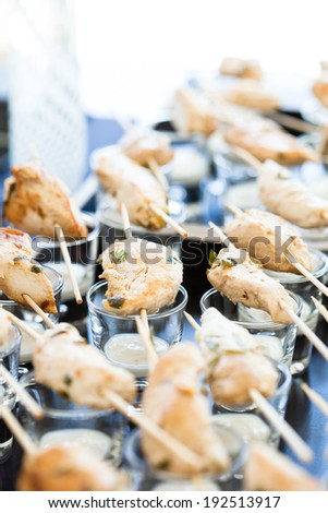 Closeup of pieces of cooked chicken on skewers with mayonnaise based condiment in glasses - stock photo