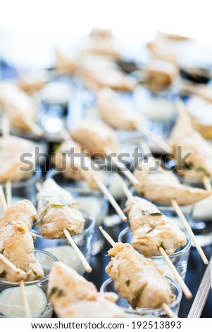 Closeup of pieces of cooked chicken on wooden skewers with mayonnaise based condiment in small glasses - stock photo