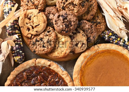 Closeup of pies and cookies for a Thanksgiving Day feast desserts. Pecan Pie, Pumpkin Pie, Chocolate Chip, oatmeal raisin and indian corn adorn the table. - stock photo