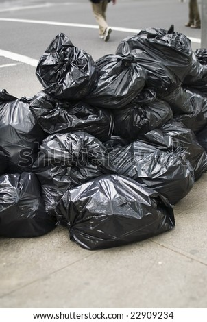 Closeup of pile of garbage bags on street - stock photo