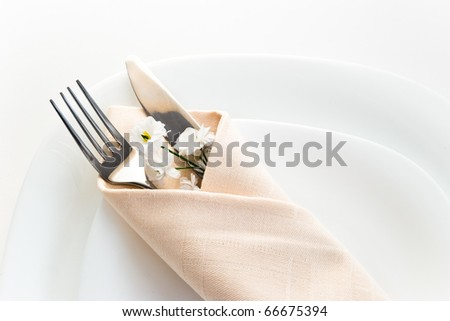 closeup of place setting with fork knife and little flower - stock photo