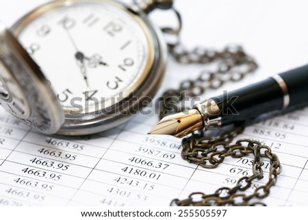 Closeup of pocket watch near fountain pen on paper background with digits - stock photo