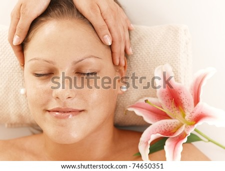 Closeup of portrait of young woman getting relaxing head massage, smiling.? - stock photo