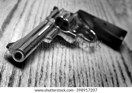Closeup of powerful handgun with bullets on old wooden surface - stock photo