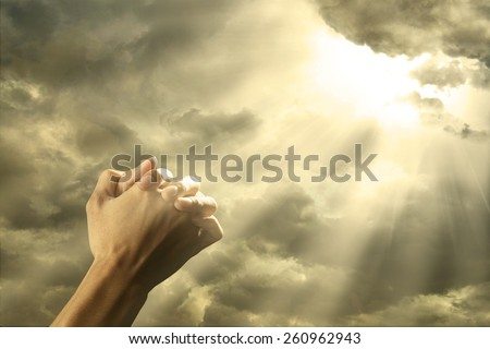 Closeup of prayer raised hands on the sky with bright rays from the cloud - stock photo