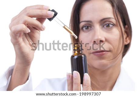 Closeup of pretty Hispanic female physician extracting a measurement of herbal tincture solution from amber bottle with glass dropper on white background  - stock photo