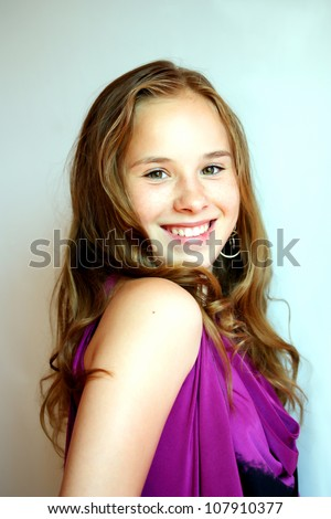 Closeup of pretty young girl smiling in the evening cocktail dress at graduation party - stock photo