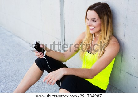 Closeup of pretty young woman sitting after workout and listening to the music from her smartphone - stock photo