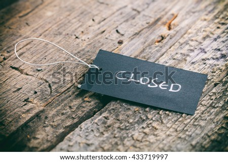 """Closeup of pricing tag with twine and """"Closed"""" text on wooden background - stock photo"""