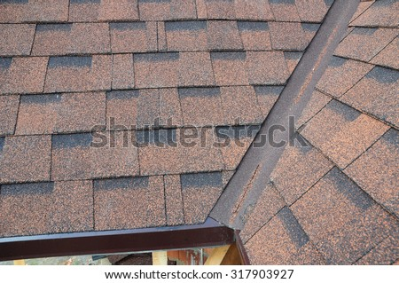 Closeup of problem areas for rain gutter waterproofing corner new installed bitumen roof shingles. - stock photo