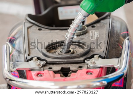 Closeup of pumping gasoline fuel into motorcycle tank - stock photo
