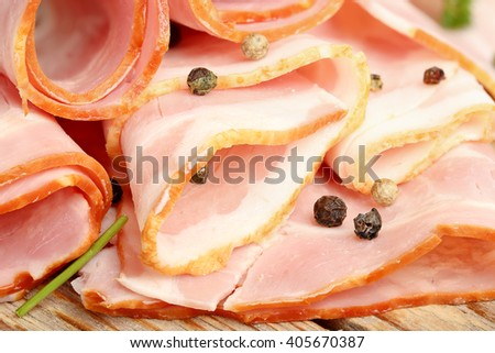 closeup of raw bacon slices with pepper - stock photo