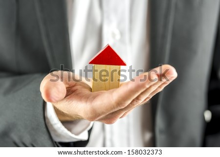Closeup of real estate agent holding a wooden  house in his hand. Real estate business.  - stock photo