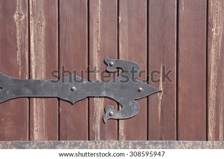 Closeup of red colored timbered fence with metal arrow. Wooden background - stock photo