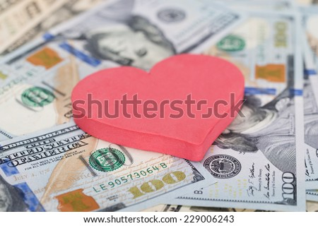 Closeup of red heart shape on dollar bills - stock photo
