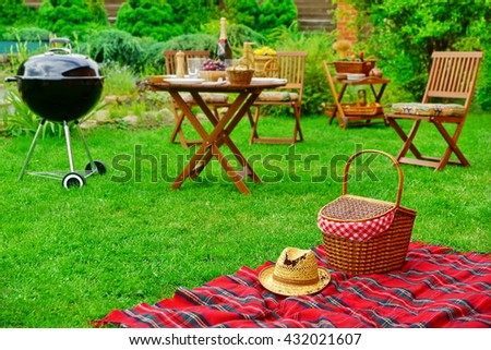Closeup Of Red Picnic Blanket With Straw Hat And Basket Or Hamper. Blurred Outdoor Wooden Furniture In The Background. Family Home Backyard BBQ Party Or Picnic Conceptual Scene - stock photo