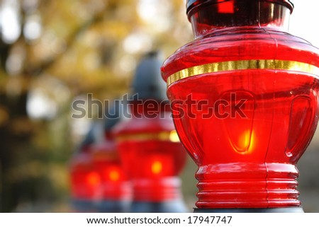 Closeup of red votive candles lit on tombstone - stock photo