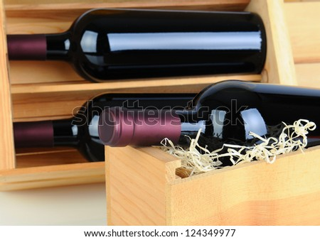 Closeup of red wine bottles in wood crates. Shallow depth of field. - stock photo