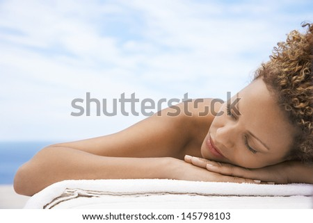 Closeup of relaxed young woman with eyes closed lying on massage table outdoors - stock photo