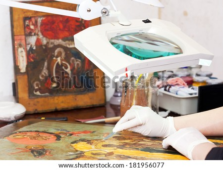 Closeup of  Restorer working on the old icon at workshop - stock photo