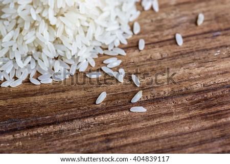 Closeup of rice on wood background - stock photo