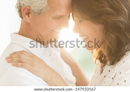 Closeup of romantic mature couple smiling outdoors - stock photo