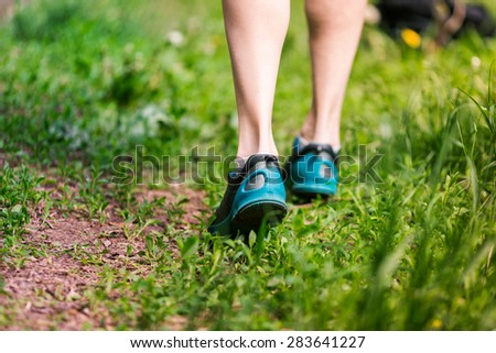 Closeup of running shoes of woman barefoot. Female jogging in the park. - stock photo