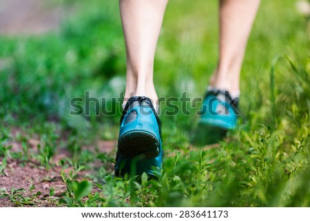 Closeup of running shoes of woman jogging in the park. - stock photo