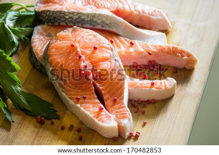closeup of salmon with red pepper on wooden board - stock photo
