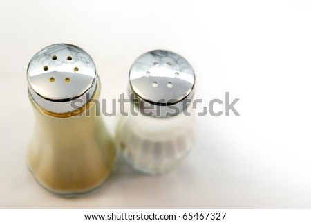 closeup of salt and pepper bottles on a table with white tablecloth - stock photo
