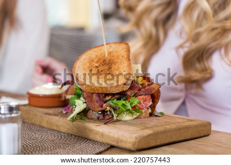 Closeup of sandwich on wooden plate with women in background - stock photo