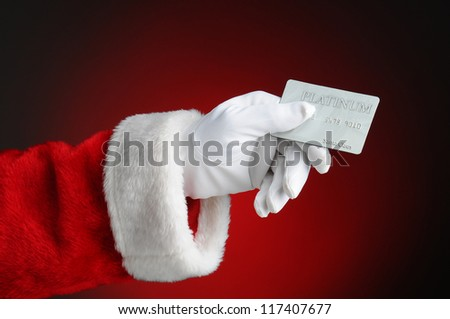 Closeup of Santa Claus hand holding a Platinum Credit Card. Horizontal format over a light to dark red background. - stock photo
