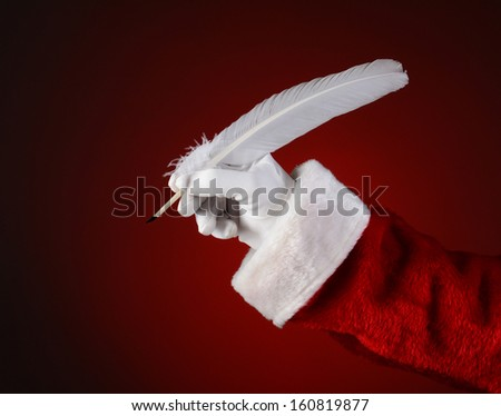 Closeup of Santa Claus holding a quill pen. Horizontal format on a light to dark red spot background. - stock photo