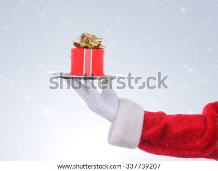 Closeup of Santas hand holding a silver tray with a wrapped Christmas Present. On a light ot dark snowy background. Horizontal format with copy space. - stock photo