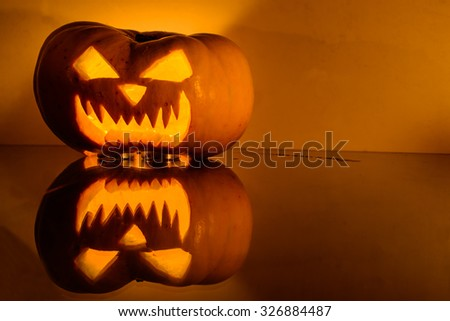 Closeup of scary Halloween pumpkin with candlelight and reflection. Shallow depth of field - stock photo