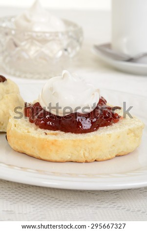 closeup of scone with cream and jam - stock photo