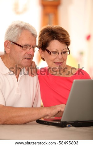 Closeup of senior couple doing online shopping - stock photo
