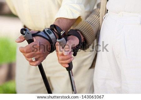 Closeup of senior couple's hands holding hiking poles - stock photo
