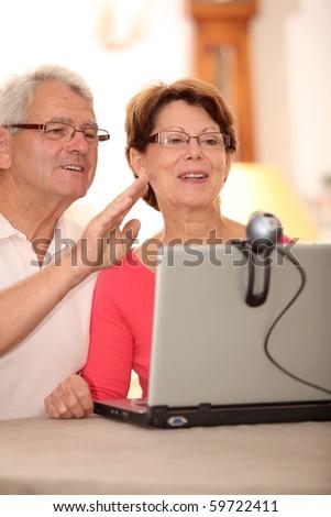 Closeup of senior couple sending messages through webcam - stock photo
