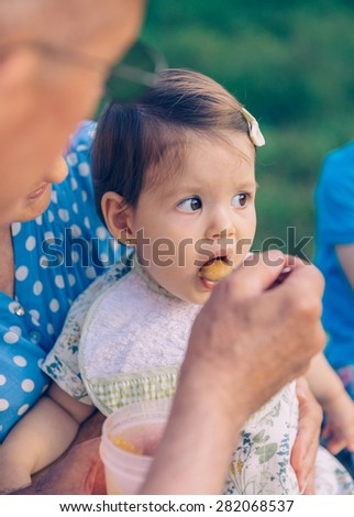Closeup of senior man feeding with fruit puree to adorable baby girl sitting over a senior woman in a bench outdoors. Grandparents and grandchildren lifestyle concept. - stock photo