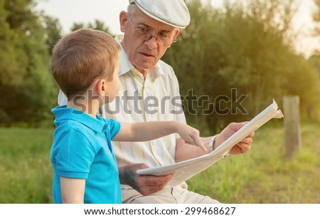 Closeup of senior man reading newspaper and cute child pointing an article with his finger sitting over a nature background. Two different generations concept. - stock photo