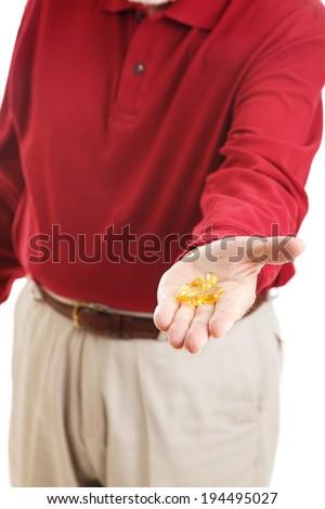 Closeup of senior man's hand holding omega-3 fish oil capsules.   - stock photo