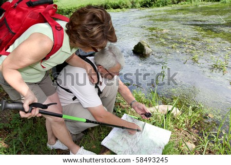 Closeup of senior people looking at map by a river - stock photo